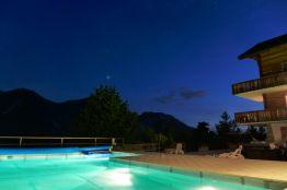 Schwimmbad mit Unterwasserbeleuchtung im Wallis