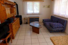 Wohnzimmer mit TV, Couche, Coutchtisch und Schwedenofen